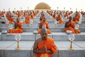 Buddhist monks pray during alms offering ceremony at the Wat Phra Dhammakaya temple in Pathum Thani province, north of Bangkok on Makha Bucha Day