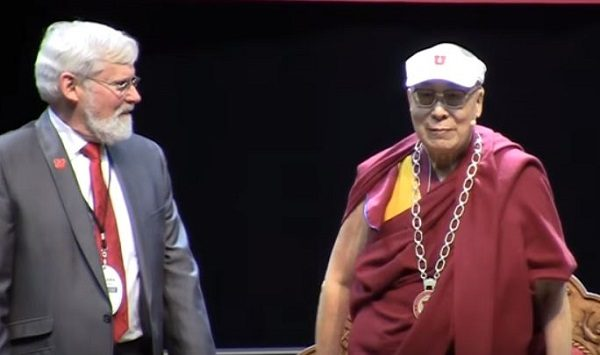 His Holiness Dalai Lama dons a University of Utah visor and honorary medal.