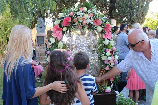Children, adults, elderly people and people with serious illnesses stand in long queues, some for hours hours in order to pray before the icon of the Assumption of Mary. Some of them. leave candles on the foot of the icon stand.