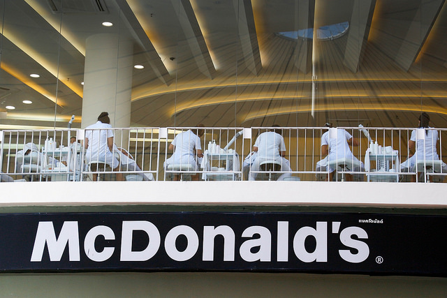 People dressed in white eating on the second floor of a mcdonalds