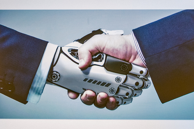 Robot hand shaking with a human hand
