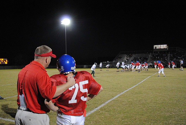 Football Coach talking to player on field