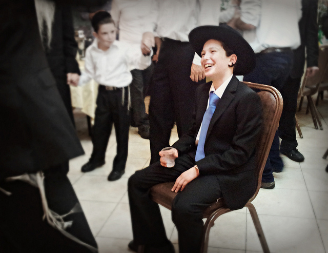 boy sitting in chair for bar mitzvah