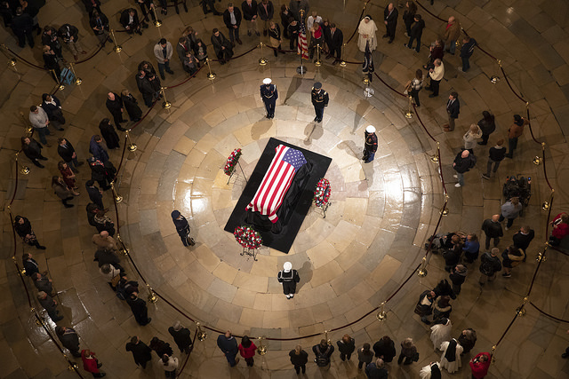 Members of the public pay their respects Monday evening, Dec. 3, 2018, at the casket of former President George H. W. Bush lying in state in the Rotunda of the U.S. Capitol in Washington, D.C. (Official White House Photo by Joyce N. Boghosian) via The White House - The United States Capitol, Public Domain, Link