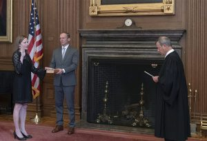 Chief Justice John G. Roberts, Jr., administers the Judicial Oath to Judge Amy Coney Barrett in the East Conference Room, Supreme Court Building. Judge Barrett's husband, Jesse M. Barrett, holds the Bible. Credit: Fred Schilling, Collection of the Supreme Court of the United States
